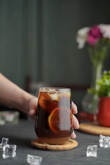 Szklanka espresso z sokiem z cytryny i świeżo pokrojoną cytryną na drewnianym stole