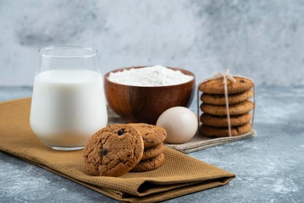 Szklanka gorącego mleka z pysznymi ciasteczkami na szarym stole.