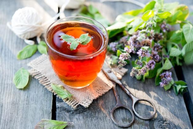 Szklanka gorącej czarnej herbaty ze świeżą miętą na rustykalnym drewnianym tle