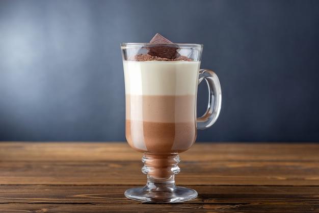 Szklanka gorącej czekolady z trzech warstw napoju na drewnianym stole. kakao, kofeina.