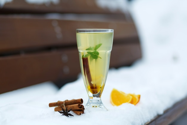 Szklanka gorącej herbaty witaminowej na zimowej ławce śnieżnej. zimowe gorące napoje sezonowe