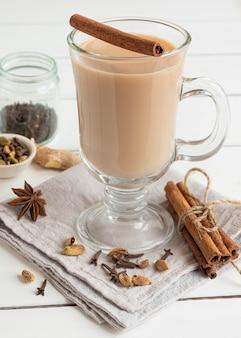 Szklanka gorącej indyjskiej herbaty masala zaparzonej z aromatycznymi przyprawami i mlekiem