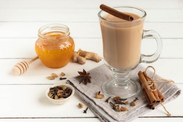 Szklanka gorącej indyjskiej herbaty masala zaparzonej z aromatycznymi przyprawami, miodem i mlekiem
