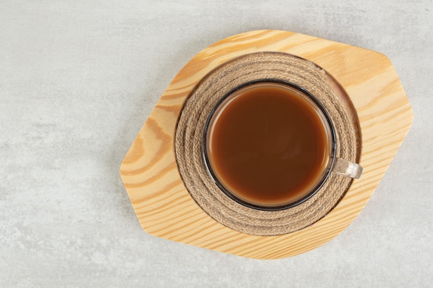 Szklanka gorącej kawy na drewnianym talerzu.