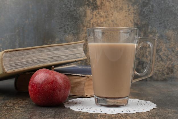 Szklanka gorącej kawy z jednym czerwonym jabłkiem i książkami na marmurowej ścianie.