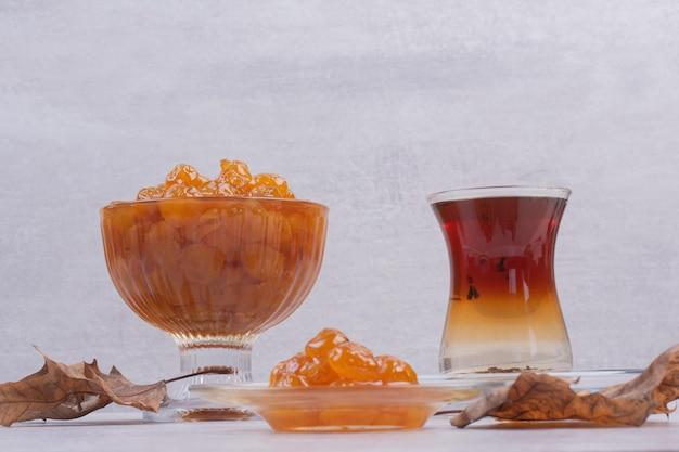 Szklanka herbaty i dżemu jagodowego na białym stole.