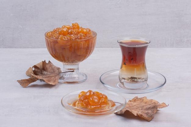 Szklanka herbaty i dżemu jagodowego na białym tle z liśćmi.
