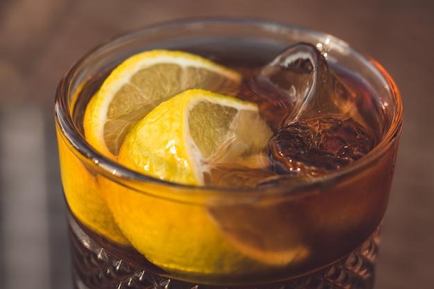 Szklanka herbaty lodowej long island z plasterkiem cytryny i słomką. napój alkoholowy z lodem w barze