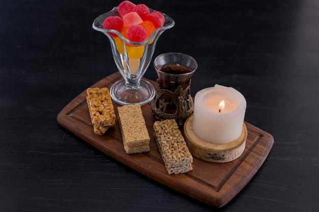 Szklanka herbaty podawana z marmoladą i waflami sezamowymi na niebieskim polu