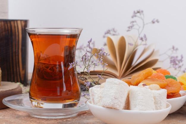 Szklanka herbaty, różne słodycze i suszone morele na marmurowym stole.