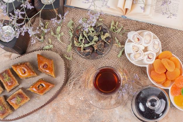 Szklanka herbaty, słodyczy i różnych tradycyjnych baklav na marmurowym stole.