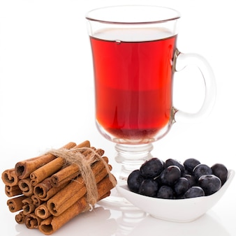 Szklanka herbaty stos cynamonu i talerz z jagodami