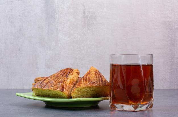 Szklanka herbaty z ciastkami na zielonym talerzu.