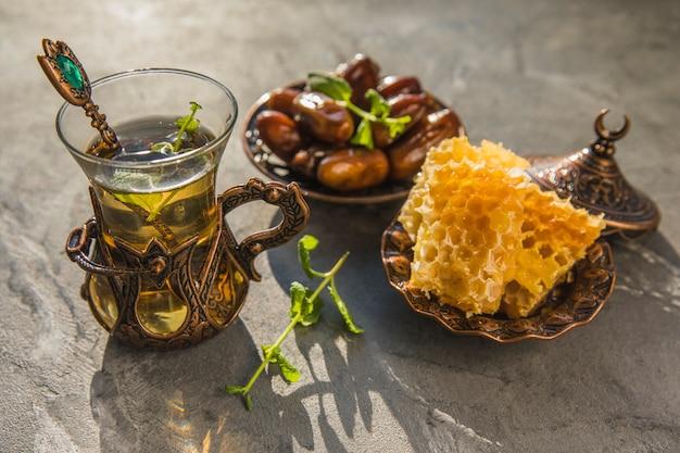 Szklanka herbaty z owocami daty i plastra miodu