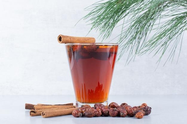 Szklanka herbaty z owocami dzikiej róży i cynamonami na szarym tle.