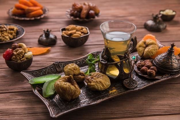 Szklanka herbaty z suszonymi figami i orzechami na tacy