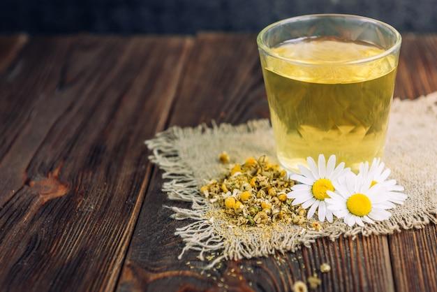 Szklanka herbaty ziołowej z kwiatów rumianku na ciemnym tle drewnianych.