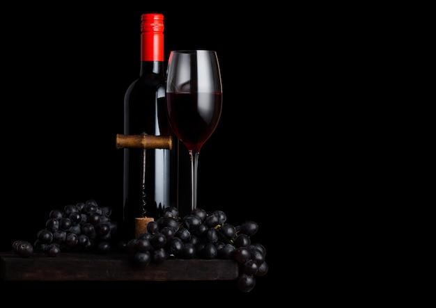 Szklanka i butelka czerwonego wina z ciemnymi winogronami i vintage korkociągiem