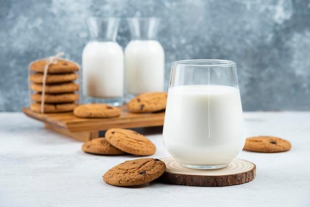 Szklanka i słoik mleka z pysznymi ciasteczkami.