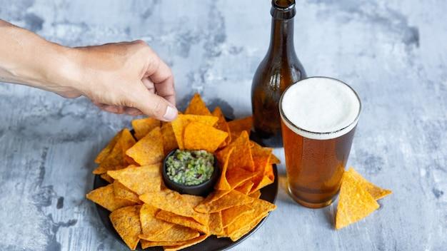 Szklanka jasnego piwa na białej kamiennej ścianie. zimny napój alkoholowy i przekąski przygotowywane są na przyjęcie dużego przyjaciela.