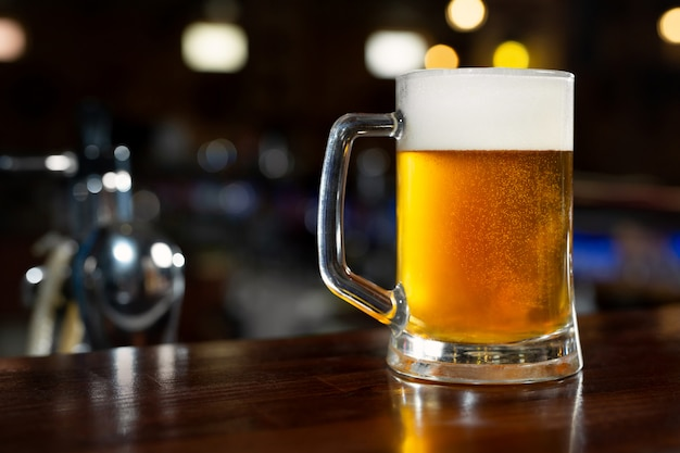 Szklanka jasnego piwa w ciemnym pubie