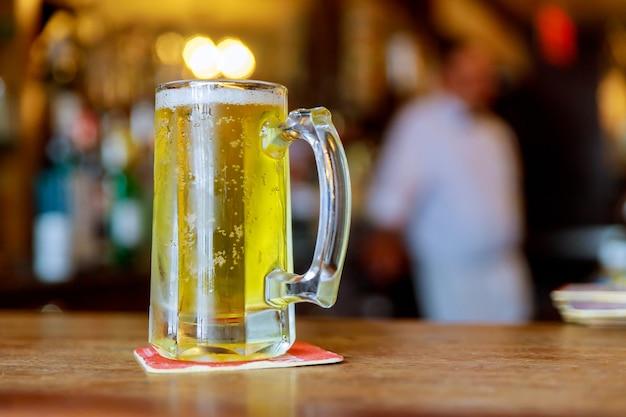 Szklanka jasnego piwa w tradycyjnym stylu pubu przy barze soft focus