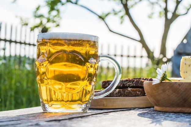 Szklanka jasnego piwa z serem i chlebem żytnim