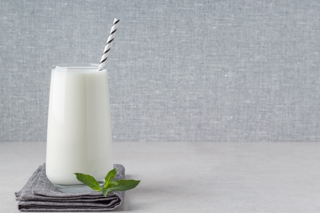 Szklanka jogurtu kefirowego lub ajranu na szarym stole pusta przestrzeń naturalny fermentowany produkt mleczny