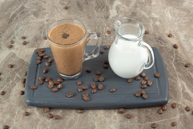 Szklanka kawy i mleka na ciemnym talerzu