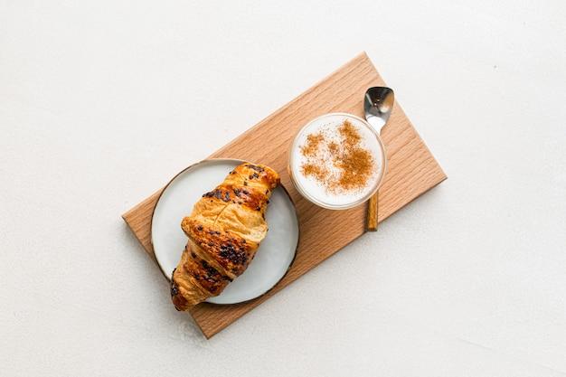 Szklanka kawy latte z cynamonem i croissantem