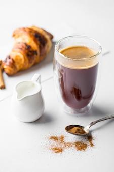 Szklanka kawy latte z rogalikiem na białym