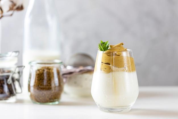 Szklanka kawy mrożonej dalgona, modnej puszystej kremowej bitej kawy, ozdobionej miętą