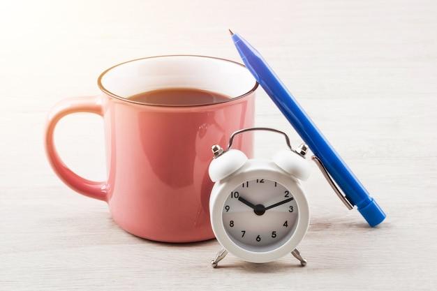 Szklanka kawy na stole z piórem i zegarem