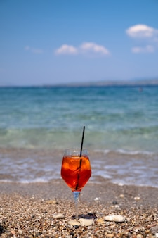 Szklanka koktajlu aperol spritz stoi na piasku w pobliżu morza