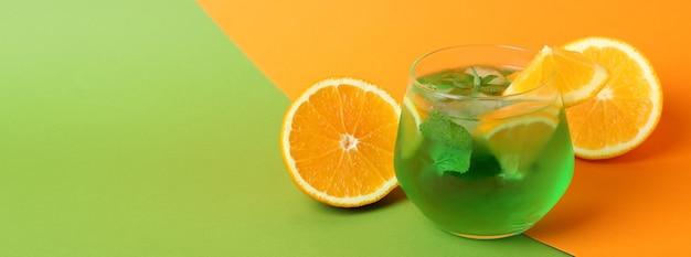 Szklanka koktajlu cytrusowego i składników na dwukolorowym tle