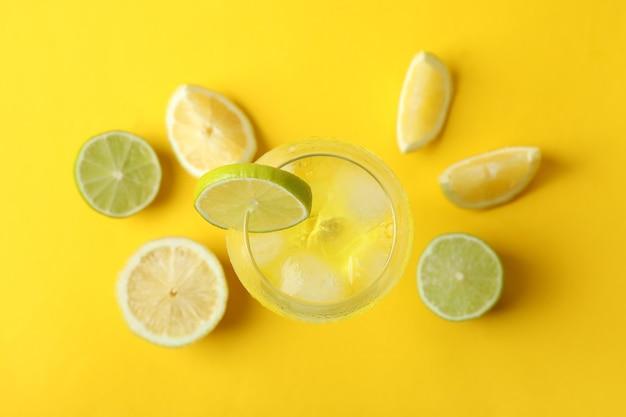 Szklanka koktajlu cytrynowego i składniki na żółtym tle