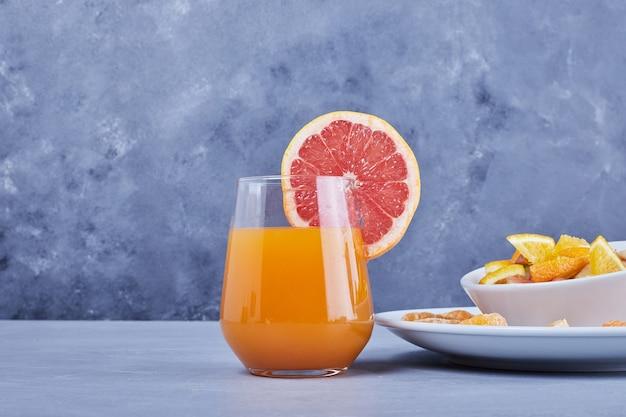 Szklanka koktajlu grejpfrutowego z sałatką owocową.