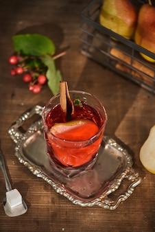 Szklanka koktajlu gruszki cydr lub lemoniady, laski cynamonu, gwiazdki anyżu na powierzchni drewnianych.