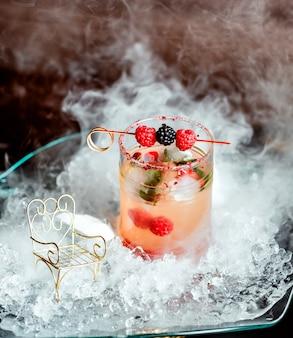 Szklanka koktajlu jagodowego przyozdobionego malinami i jeżynami na szaszłykach