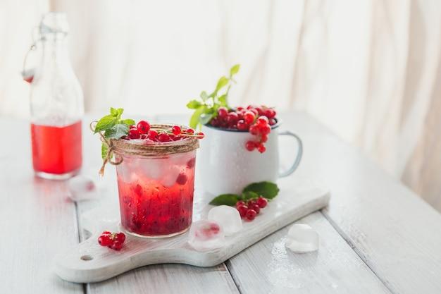 Szklanka koktajlu lub bezalkoholu z czerwonej porzeczki, orzeźwiający letni napój z kruszonym lodem i gazowaną wodą na białej drewnianej powierzchni
