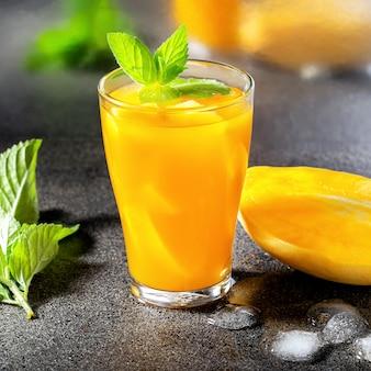 Szklanka koktajlu mango z miętą na kontuarze.