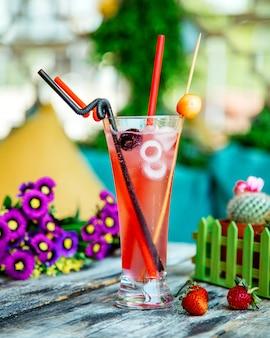 Szklanka koktajlu wiśniowego z lodem i plastikowymi rurkami ze słomy
