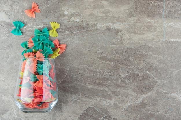 Szklanka kolorowej farfalle na marmurowej powierzchni