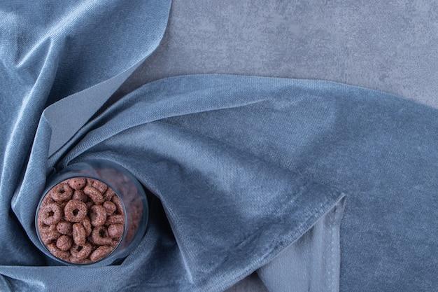 Szklanka krążków kukurydzy na kawałku tkaniny na niebieskim stole.