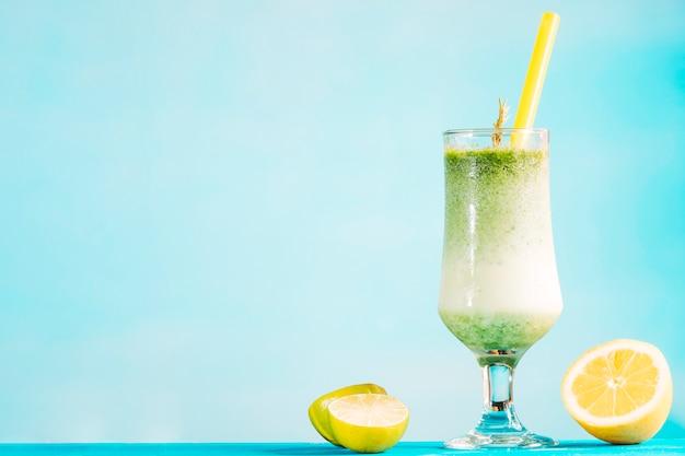 Szklanka kremowego, zielonego smoothie i plasterków cytrusów