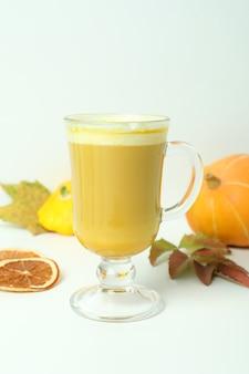 Szklanka latte z dyni i składniki na białym tle
