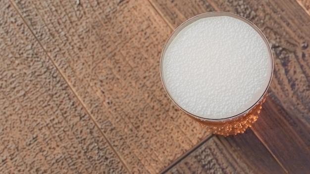 Szklanka lekkiego piwa na drewnianym stole., model 3d i ilustracja.