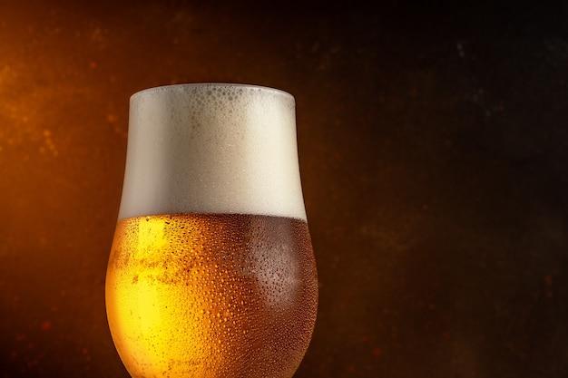 Szklanka lekkiego piwa na drewnianym stole.