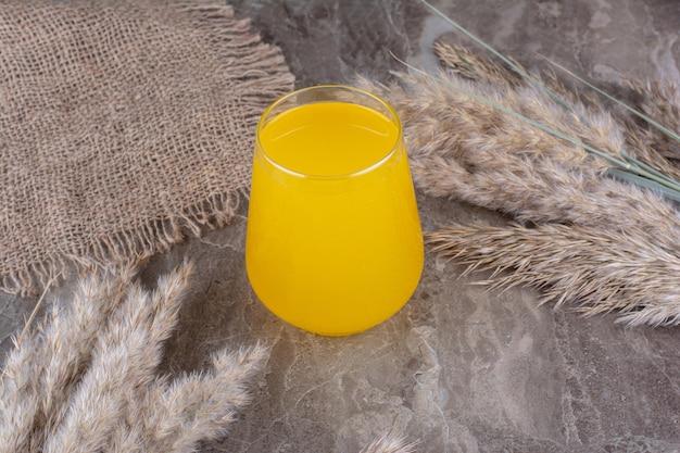 Szklanka lemoniady z kłosami pszenicy na marmurowym stole