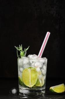 Szklanka lemoniady z limonki na ciemnym tle. ramka pionowa, selektywne ustawianie ostrości. domowy napój z limonką, estragonem, wodą mineralną i kostkami lodu. pomysł na zimną świeżą lemoniadę
